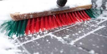 Besen im Schnee, Winterdienst, Schneeräumen, Bürgersteig